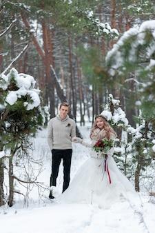 Vrolijke bruid en bruidegom in beige gebreide truien lopen in het besneeuwde bos. winter bruiloft