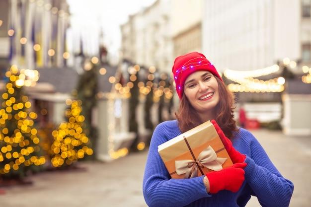 Vrolijke brunette dame draagt rode hoed en blauwe trui met geschenkdoos op de kerstmarkt versierd met slingers. ruimte voor tekst