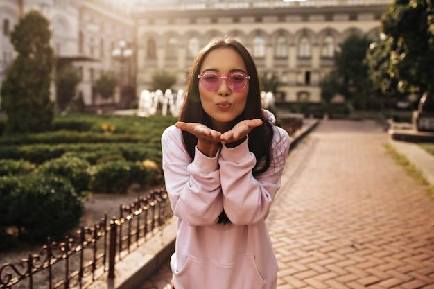 Vrolijke brunette dame in kleurrijke zonnebril en roze hoodie poseert in een goed humeur buiten en blaast kus