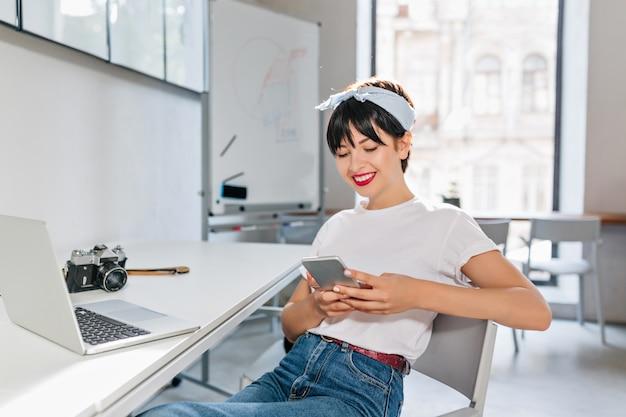Vrolijke brunette dame in wit overhemd en spijkerbroek werken met laptop in grote moderne kantoren