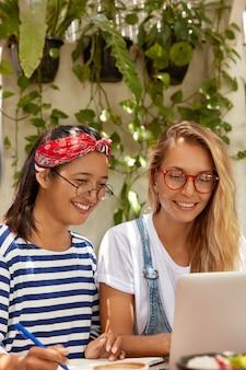 Vrolijke brunette en blonde meisjes gebruiken moderne laptop voor entertainment en studeren, besteden samen vrije tijd