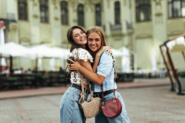 Vrolijke brunette en jonge blonde vrouwen in stijlvolle spijkerbroeken en kleurrijke blouses verheugen zich, hebben plezier, glimlachen wijd buitenshuis