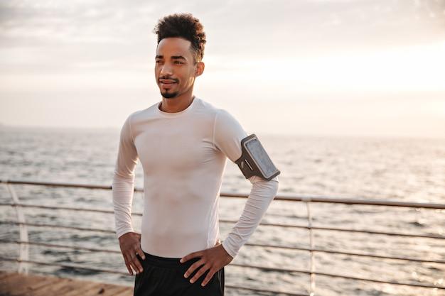 Vrolijke brunette gekrulde donkere man in wit t-shirt en zwarte sportbroek staat in de buurt van zee en kijkt in de verte