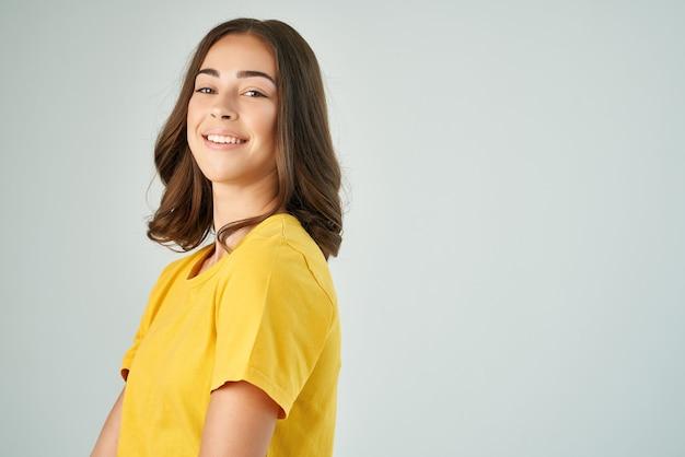 Vrolijke brunette in gele tshirt poseren glimlach bijgesneden weergave geïsoleerde achtergrond