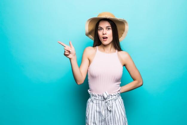 Vrolijke brunette in wit t-shirt en bril aan de muur. van blauw toont een vinger opzij