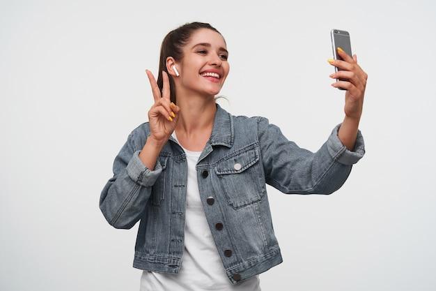 Vrolijke brunette jongedame draagt in wit t-shirt en denim jacks, houdt smartphone en maakt selfie met vredesgebaar. staat op een witte achtergrond.