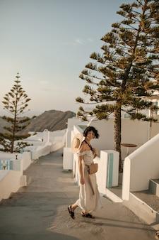 Vrolijke brunette krullende vrouw in midi beige jurk glimlacht oprecht buiten