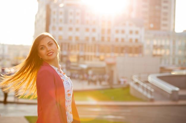 Vrolijke brunette meisje met fladderende haren poseren op de achtergrond wazig stad. ruimte voor tekst