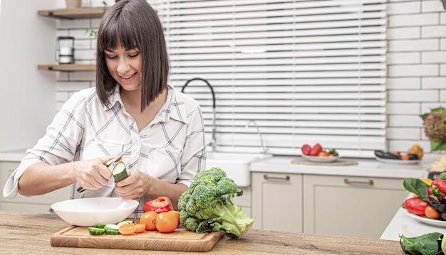 Vrolijke brunette meisje snijdt groenten op salade op de ruimte van het moderne keuken interieur.
