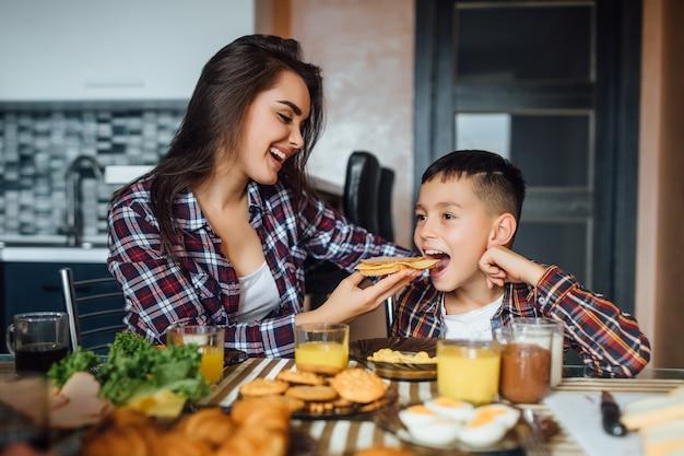 Vrolijke brunette moeder haar zoon sandwich voederen met kaas tijdens het ontbijt thuis