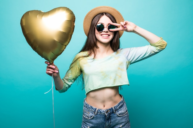 Vrolijke brunette mooie dame in jurk met gouden luchtballon als hart en geïsoleerd vredesgebaar tonen