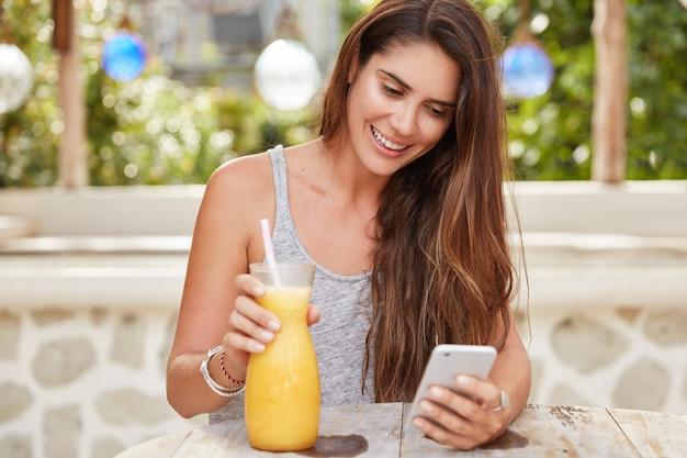 Vrolijke brunette vrouw bekijkt video op internetwebsite, stuurt feedback op slimme telefoon, gekleed in informele kleding, drinkt sinaasappelsap, recreëert in openluchtcafetaria.