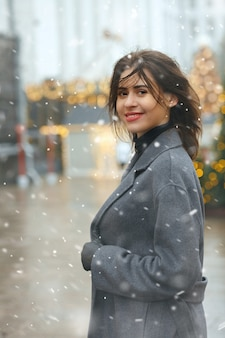 Vrolijke brunette vrouw draagt een trendy jas die tijdens de sneeuwval door de stad loopt die versierd is met kerstmis