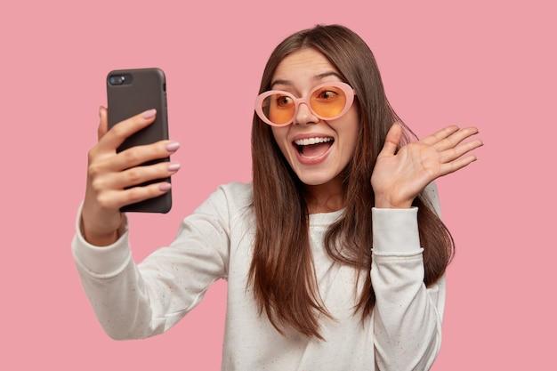 Vrolijke brunette vrouw draagt een zonnebril, voert een videogesprek, is verbonden met draadloos internet, gekleed in een witte trui, geïsoleerd over roze muur. hallo vriend