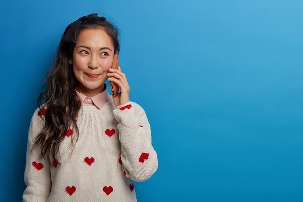 Vrolijke brunette vrouw glimlacht gelukkig, heeft telefoongesprek, houdt smartphone in de buurt van oor, draagt trui, geniet van leuke praatjes, geïsoleerd op blauwe muur, kopieer ruimte opzij voor uw promotie