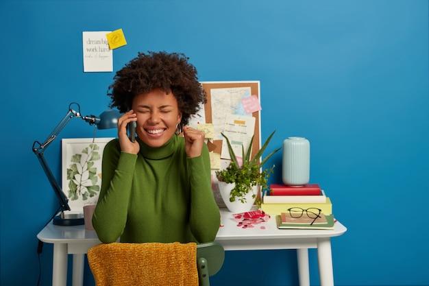 Vrolijke brunette vrouw heeft een aangenaam gesprek, proost met opgeheven vuist, verheugt zich op het voltooide project, vormt in de buurt van de werkplek thuis, sluit de ogen van plezier, geïsoleerd op blauwe muur.