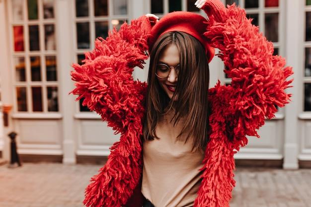 Vrolijke brunette vrouw in glazen danst tegen ramen in witte frames. vrouw in beige t-shirt, rode baret en jas heeft plezier op straat.