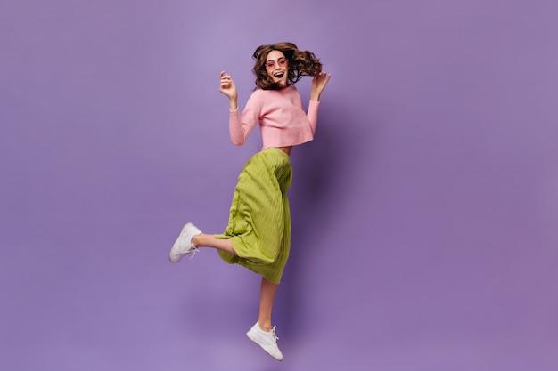 Vrolijke brunette vrouw in groene rok en roze trui springt op paarse muur