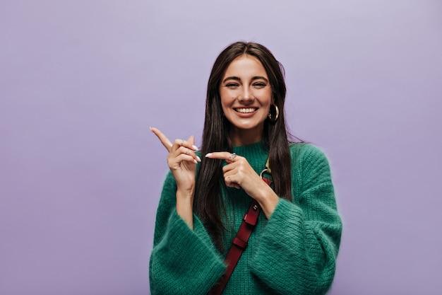 Vrolijke brunette vrouw in groene stijlvolle wollen trui glimlacht oprecht