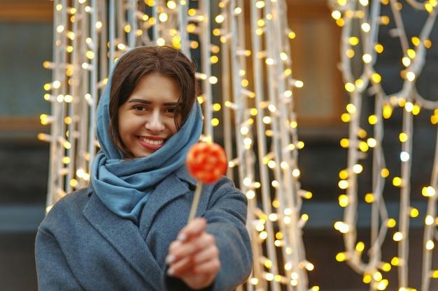 Vrolijke brunette vrouw in jas met snoep op de kerstmarkt. ruimte voor tekst