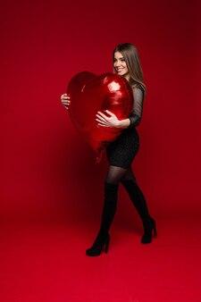Vrolijke brunette vrouw in jurk en laarzen met rode hartvormige ballon