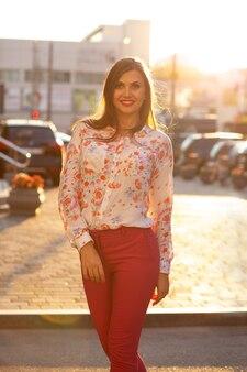 Vrolijke brunette vrouw in kostuum en blouse poseren met zacht avondzonlicht