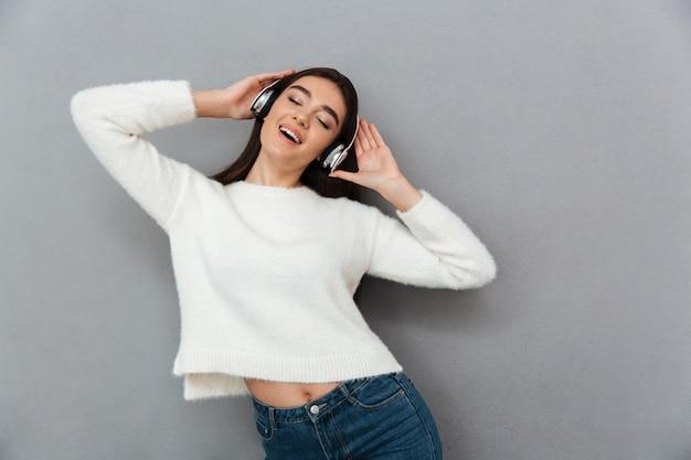 Vrolijke brunette vrouw in trui en koptelefoon luisteren muziek