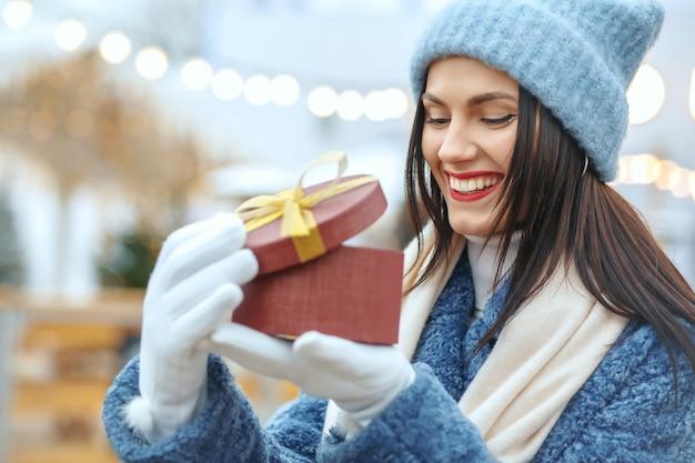 Vrolijke brunette vrouw in winterjas met een geschenkdoos op kerstmarkt. ruimte voor tekst