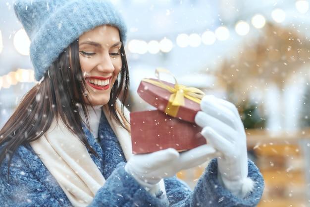 Vrolijke brunette vrouw in winterjas met een geschenkdoos op kerstmarkt tijdens de sneeuwval. ruimte voor tekst