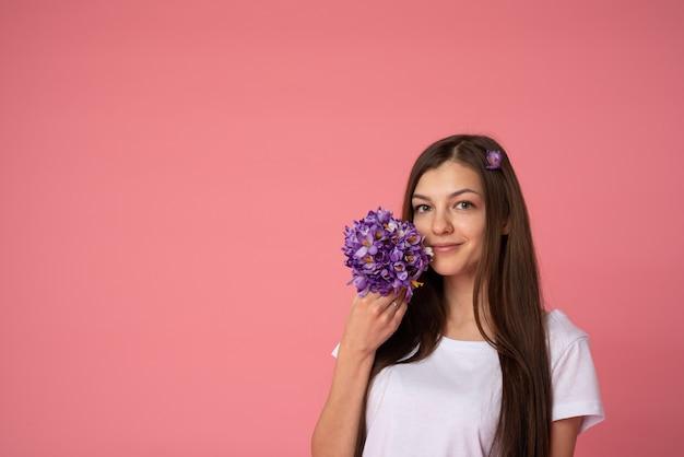 Vrolijke brunette vrouw in wit t-shirt met sneeuwklokjes lentebloemen