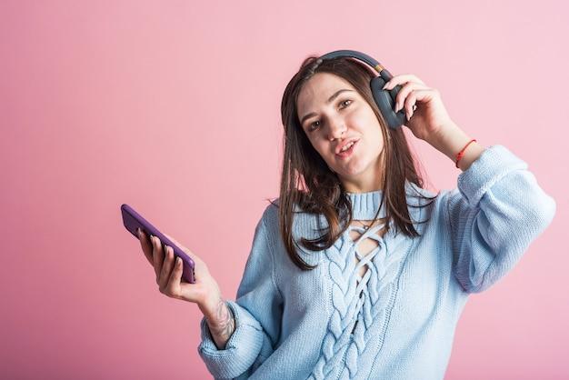 Vrolijke brunette vrouw luistert naar muziek in hoofdtelefoons met een smartphone in de studio op een roze achtergrond
