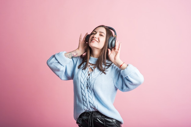 Vrolijke brunette vrouw luistert naar muziek op de koptelefoon in de studio op een roze achtergrond