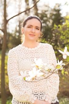 Vrolijke brunette vrouw met naakt make-up, het dragen van kanten blouse, poseren in de buurt van de bloeiende magnolia bloemen