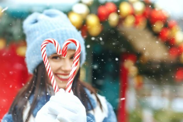Vrolijke brunette vrouw met snoepjes in de vorm van een hart tijdens de sneeuwval. ruimte voor tekst