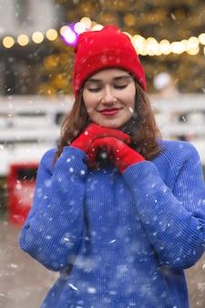 Vrolijke brunette vrouw wandelen op kerstmarkt tijdens de sneeuwval