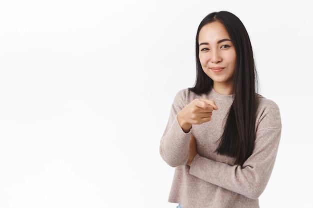 Vrolijke brutale en zelfverzekerde aziatische vrouw die keuze maakt, je kiest, camera richt en tevreden glimlacht, nodigt uit voor een interview om haar bedrijf te werken