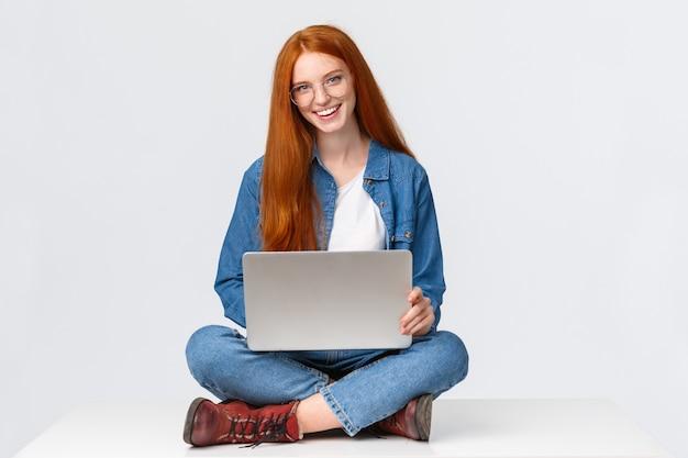 Vrolijke brutale roodharige vrouwelijke student, college meisje in glazen, zittend op gekruiste benen met laptop, freelance werken, project awat voorbereiden vanuit kantoor, afstandsbediening op witte achtergrond.