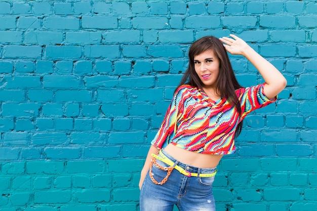 Vrolijke buikdanseres dansen met arabische muziek op blauwe bakstenen muur met kopie ruimte