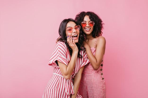 Vrolijke, buitengewone meisjes in schattige roze jurkjes hebben plezier. mooie dames genieten van fotoshoot.