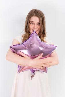 Vrolijke buitensporige vrouw die ballon omhelst