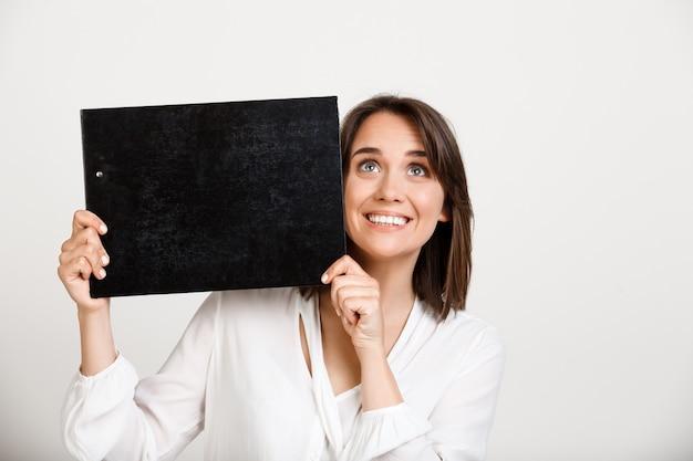 Vrolijke bureaudame die banner op zwart klembord tonen