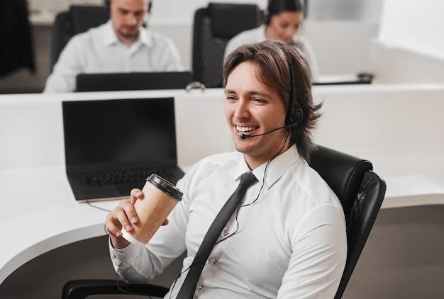 Vrolijke callcentermedewerker met afhaalkoffie
