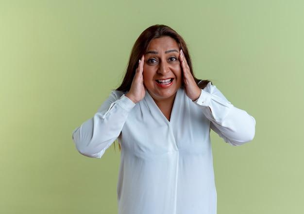 Vrolijke casual blanke vrouw van middelbare leeftijd handen op de wang te zetten geïsoleerd op olijfgroen