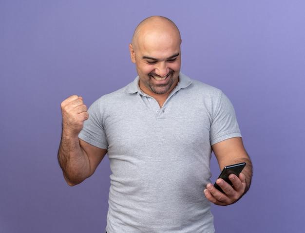 Vrolijke, casual man van middelbare leeftijd die een mobiele telefoon vasthoudt en bekijkt die ja-gebaar doet geïsoleerd op een paarse muur