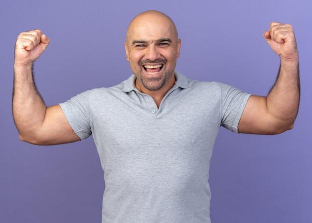 Vrolijke casual man van middelbare leeftijd die naar de voorkant kijkt en ja gebaar doet geïsoleerd op paarse muur