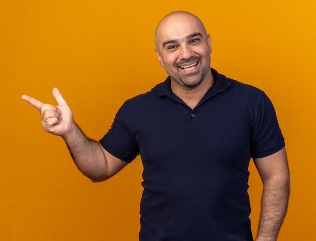 Vrolijke, casual man van middelbare leeftijd die naar de voorkant kijkt en naar de zijkant wijst geïsoleerd op een oranje muur