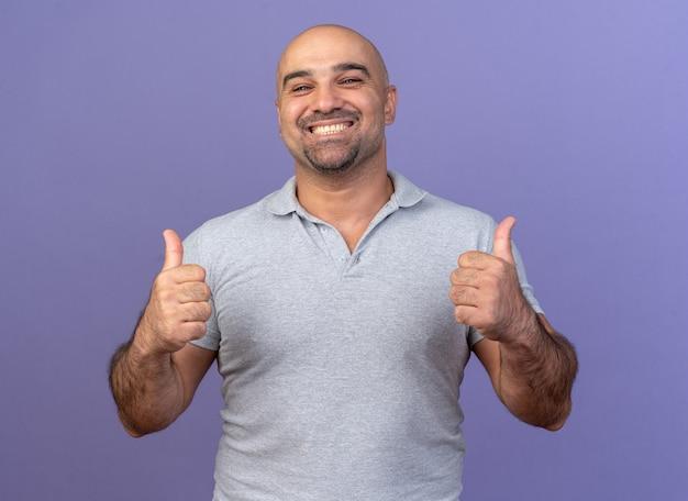 Vrolijke casual man van middelbare leeftijd met duimen omhoog geïsoleerd op paarse muur