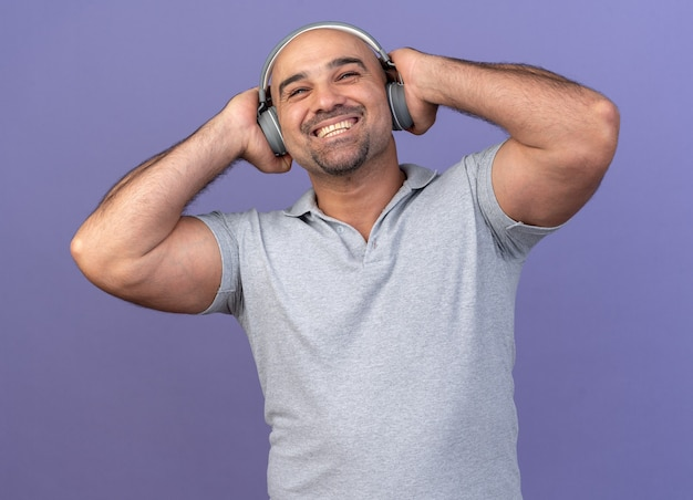 Vrolijke casual man van middelbare leeftijd met een koptelefoon die de handen op hen houdt en omhoog kijkt geïsoleerd op de paarse muur