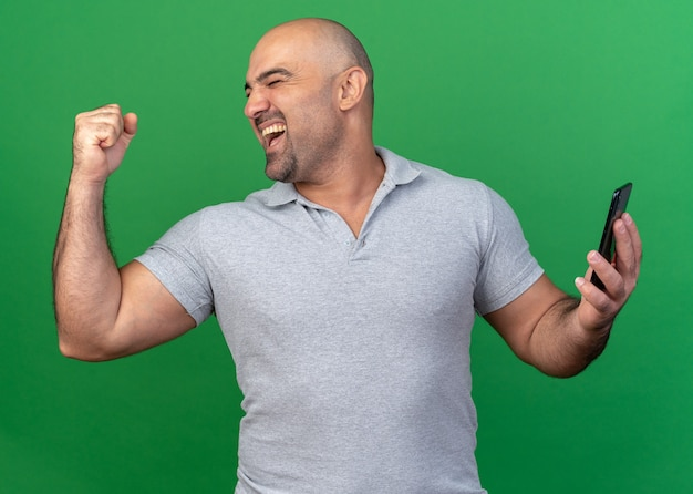 Vrolijke, casual man van middelbare leeftijd met mobiele telefoon die ja-gebaar doet met gesloten ogen geïsoleerd op groene muur