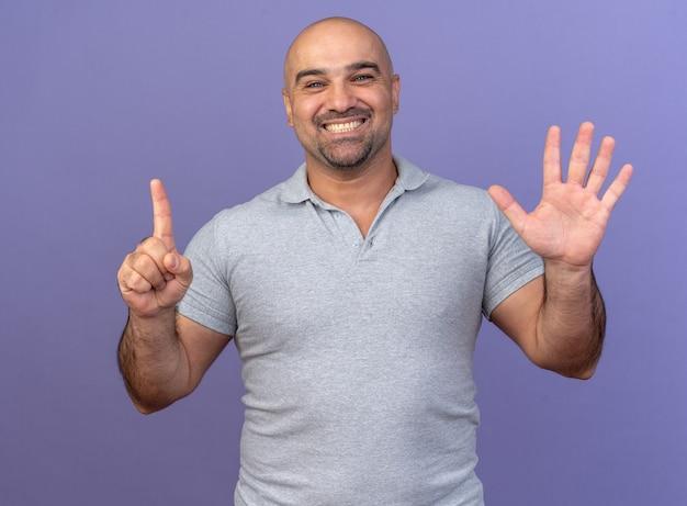 Vrolijke casual man van middelbare leeftijd met zes met handen geïsoleerd op paarse muur